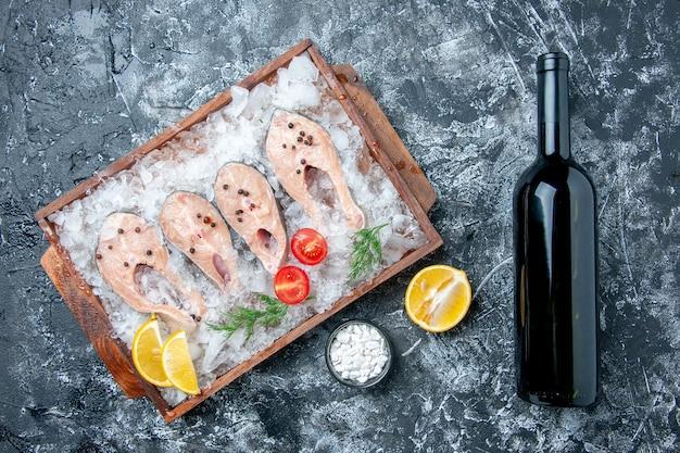 Vista de cima fatias de peixe cru com gelo na tábua de madeira sal marinho em uma pequena tigela com garrafa de vinho na mesa