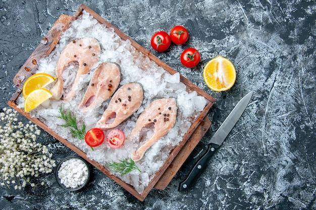 Vista de cima fatias de peixe cru com gelo na tábua de madeira sal marinho em uma pequena tigela de faca no espaço livre da mesa
