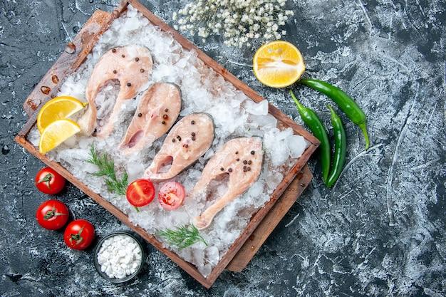 Vista de cima fatias de peixe cru com gelo na tábua de madeira sal marinho em uma tigela pequena de legumes na mesa