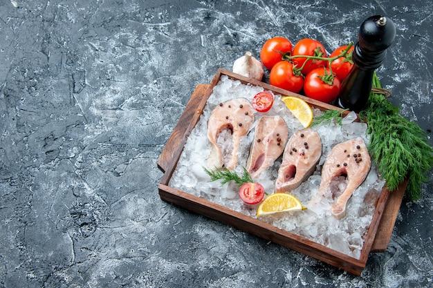 Vista de cima fatias de peixe cru com gelo na tábua de madeira, tomate, alho, endro, mesa, copie, lugar