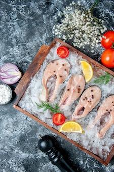 Vista de cima fatias de peixe cru com gelo na tábua de madeira tomate cebola na mesa
