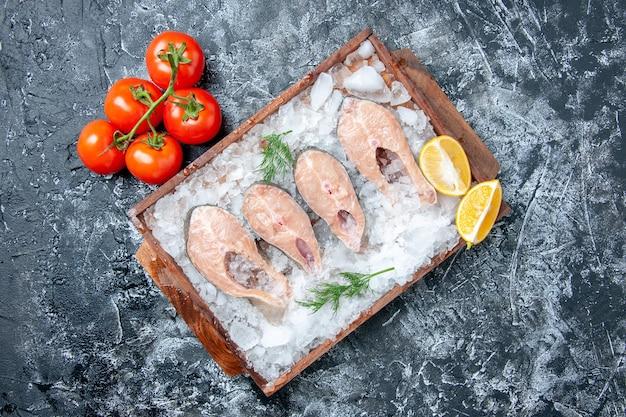 Vista de cima fatias de peixe cru com gelo na tábua de madeira, tomate fresco no espaço livre da mesa