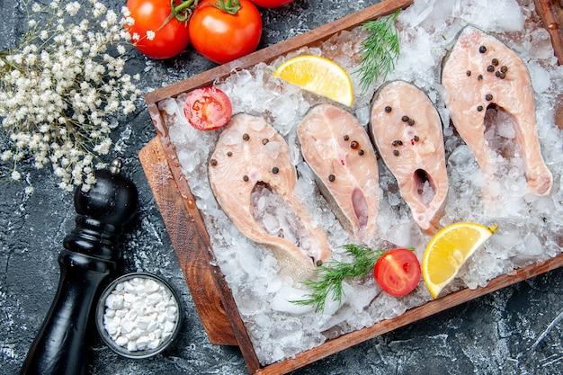 Vista de cima fatias de peixe cru com gelo na tábua de madeira tomate sal marinho em uma tigela pequena moedor de pimenta na mesa