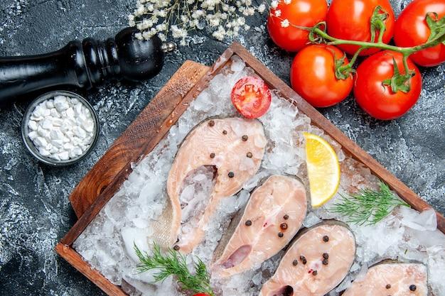 Vista de cima fatias de peixe cru com gelo na tábua de madeira tomate sal marinho em uma tigela pequena na mesa
