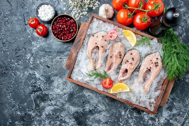 Vista de cima fatias de peixe cru com gelo na tábua de madeira tomates alho endro sal marinho sementes de romã em tigelas na mesa