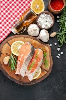 Vista de cima fatias de peixe fresco com fatias de limão, alho e temperos na mesa escura