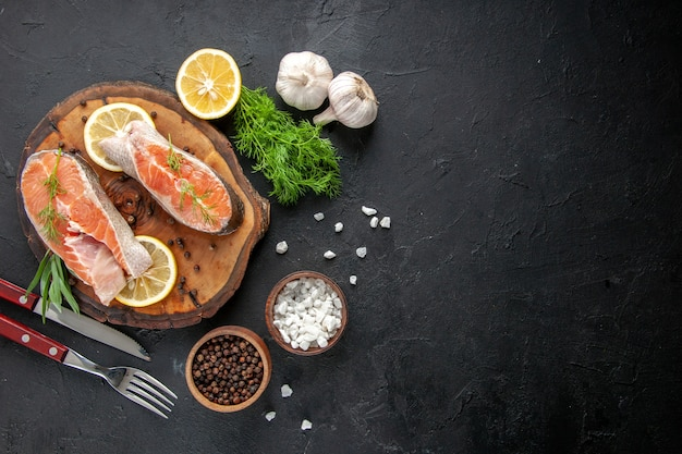 Vista de cima fatias de peixe fresco com rodelas de limão e alho na mesa escura