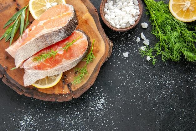 Vista de cima fatias de peixe fresco com rodelas de limão na mesa escura prato de frutos do mar cor comida carne crua