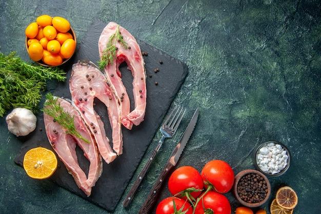 Vista de cima fatias de peixe fresco com tomates verdes e kumquats em fundo escuro