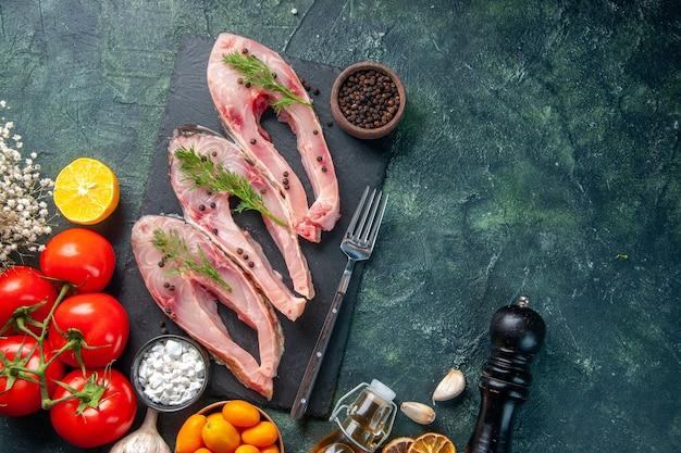 Vista de cima fatias de peixe fresco com tomates vermelhos e kumquats em fundo escuro