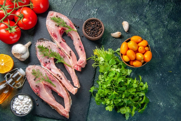 Vista de cima fatias de peixe fresco com tomates vermelhos e verduras em fundo escuro