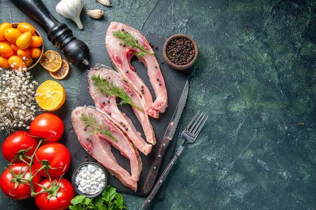 Vista de cima fatias de peixe fresco com tomates vermelhos em fundo escuro