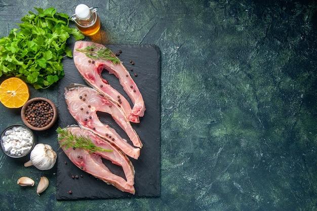 Vista de cima fatias de peixe fresco com verduras em fundo azul escuro