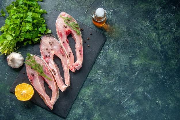 Vista de cima fatias de peixe fresco com verduras em fundo escuro
