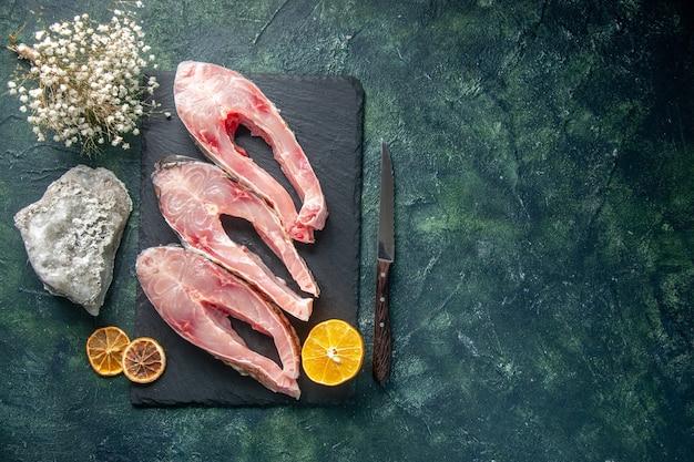 Vista de cima fatias de peixe fresco em fundo escuro