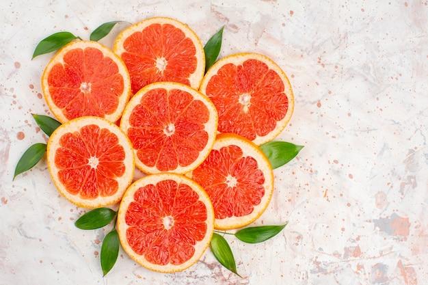 Vista de cima fatias deliciosas de toranjas na mesa de nude com espaço de cópia