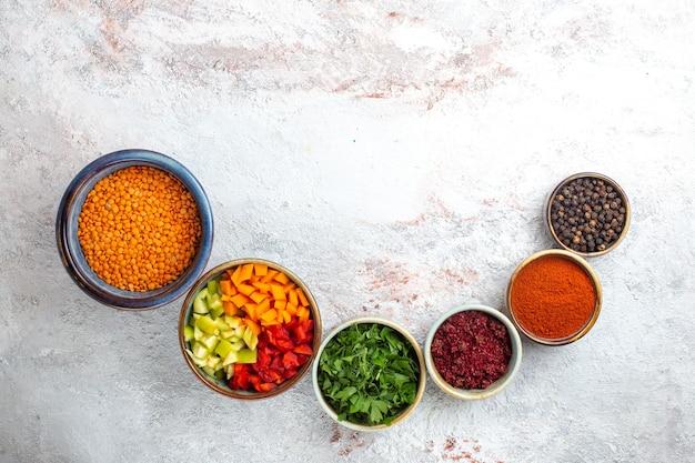 Vista de cima feijão de laranja cru com temperos na superfície branca clara feijão merci ingrediente vegetal