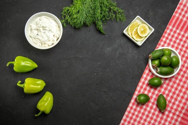 Vista de cima feijoa e limão com pimentão verde e verduras na superfície escura