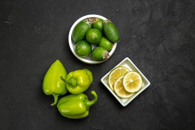 Vista de cima feijoa verde fresca com rodelas de limão e pimentão verde na superfície escura frutas vegetais cítricos planta suave