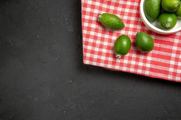 Vista de cima feijoa verde fresca frutas exóticas na superfície escura frutas exóticas saúde suave
