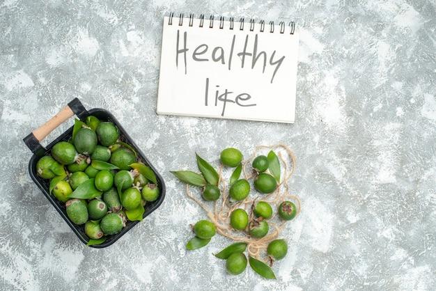 Vista de cima feykhoas frescas na cesta de vida saudável escrita no bloco de notas na superfície cinza