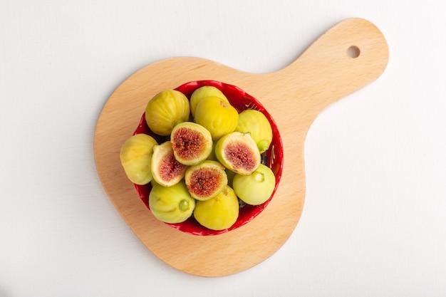 Vista de cima, figos doces e figos deliciosos fetos dentro de uma placa vermelha na mesa branca