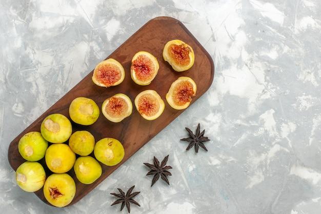 Vista de cima, figos doces e frutas deliciosas em uma mesa branca clara