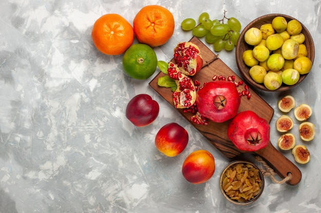 Vista de cima figos frescos com romãs, pêssegos e uvas na mesa branca