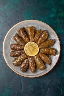 Vista de cima folha dolma deliciosa refeição de carne oriental enrolada dentro de folhas verdes na mesa azul escuro refeição de carne comida jantar vegetais saúde caloria
