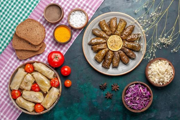 Vista de cima folha dolma refeição de carne oriental enrolada dentro de folhas verdes com pão e dolma de repolho em mesa azul escuro prato de jantar carne refeição oriental