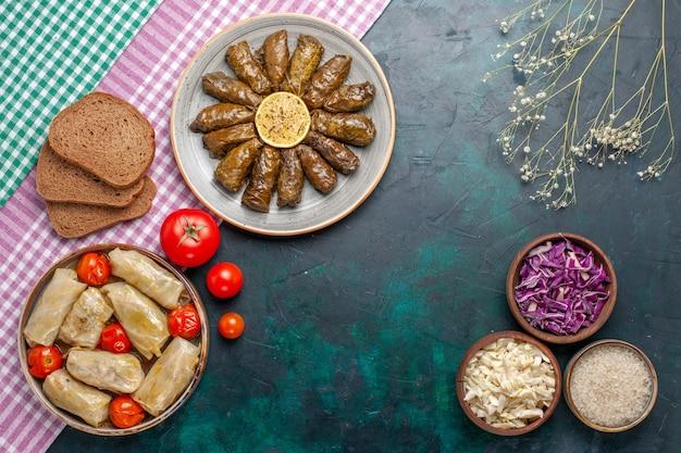 Vista de cima folha dolma refeição de carne oriental enrolada dentro de folhas verdes com pão e dolma de repolho na mesa azul-escura carne prato de jantar refeição oriental