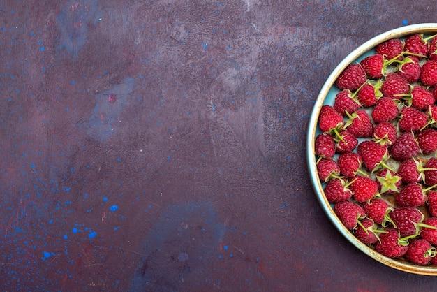Vista de cima framboesas vermelhas frescas bagas maduras e azedas em fundo azul escuro vitamina alimentar suave de frutas vermelhas