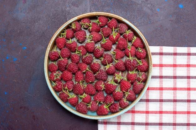 Vista de cima framboesas vermelhas frescas bagas suaves dentro de uma tigela redonda na superfície escura frutas bagas frescas