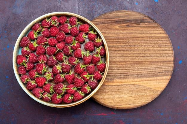 Vista de cima, framboesas vermelhas frescas e frutas maduras na mesa azul-escura.