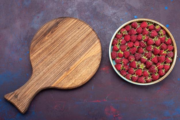 Vista de cima, framboesas vermelhas frescas e frutas maduras no fundo azul escuro. vitamina alimentar suave de frutas vermelhas