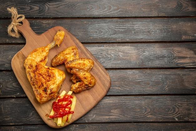 Vista de cima frango com batatas fritas frango apetitoso com batatas fritas e ketchup na tábua de corte do lado esquerdo da mesa de madeira