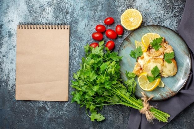 Vista de cima frango com queijo no prato bando de salsa meio limão, tomate cereja, bloco de notas na mesa cinza