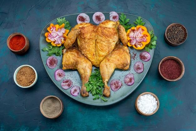 Vista de cima frango cozido com cebola e verduras dentro do prato na mesa azul escura frango assar carne no forno