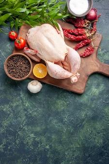 Vista de cima frango cru fresco com tomates vermelhos em fundo azul escuro refeição de cozinha foto de animais frango fazenda cor de carne