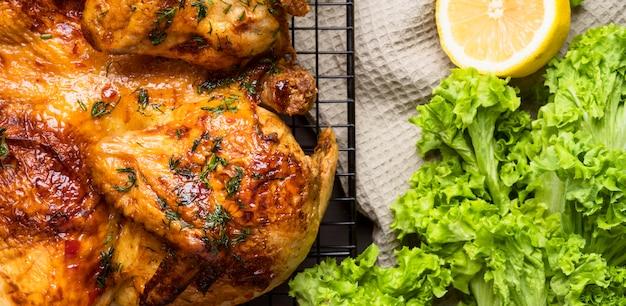 Vista de cima frango inteiro assado com salada e limão