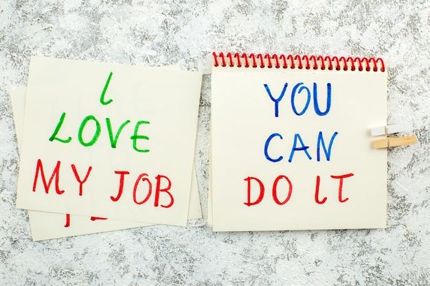 Vista de cima frases inspiradoras escritas em papéis de anotações em fundo branco cinza eu amo meu trabalho