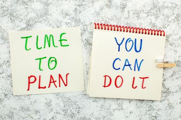 Vista de cima frases inspiradoras escritas em papéis de anotações sobre fundo branco cinza, hora de planejar