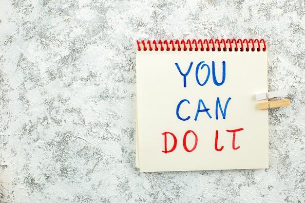 Vista de cima frases inspiradoras que você pode fazer escritas no bloco de notas no local de cópia de fundo cinza branco