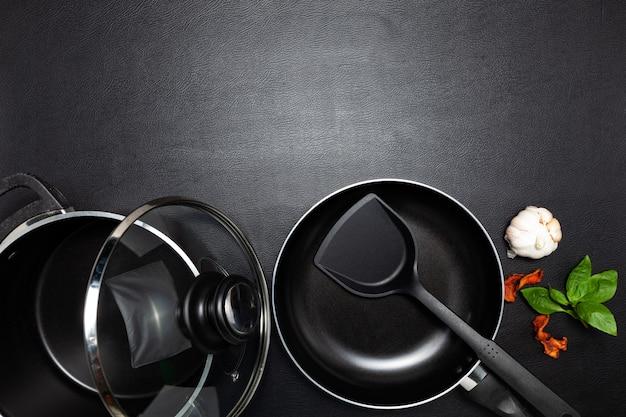 Vista de cima frigideira e panela no fundo da mesa de couro preto