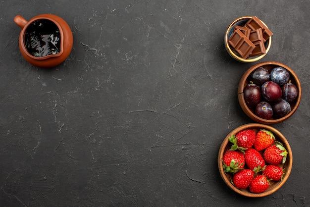 Vista de cima, frutas e doces, molho de chocolate, morangos, chocolate e frutas vermelhas em tigelas marrons na mesa escura