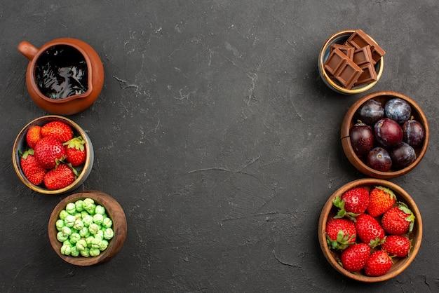 Vista de cima, frutas e doces, morango, molho de chocolate, morangos, chocolate verde, doces e frutas vermelhas em tigelas marrons sobre a mesa