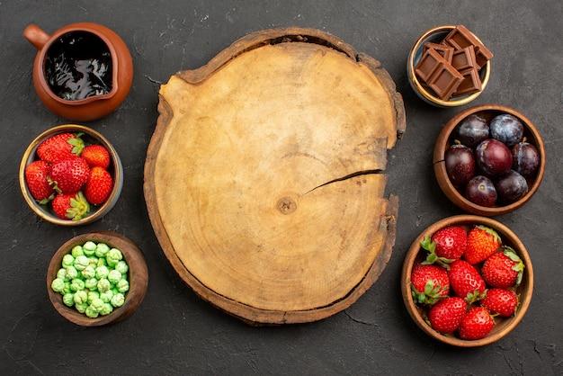 Vista de cima frutas e doces tábua de madeira entre morangos com molho de chocolate, chocolate verde, doces e frutas em tigelas marrons sobre a mesa