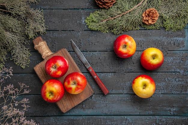 Vista de cima frutas e faca três maçãs amarelo-avermelhadas na tábua de madeira ao lado de uma faca e três maçãs sob os banchos das árvores com cones na mesa