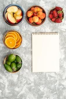 Vista de cima frutas fatiadas, maçãs e laranjas com feijoa em um fundo branco frutas frescas vitaminas maduras saudáveis