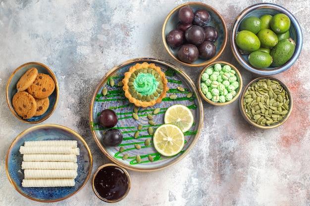 Vista de cima frutas frescas com biscoitos e bolinho